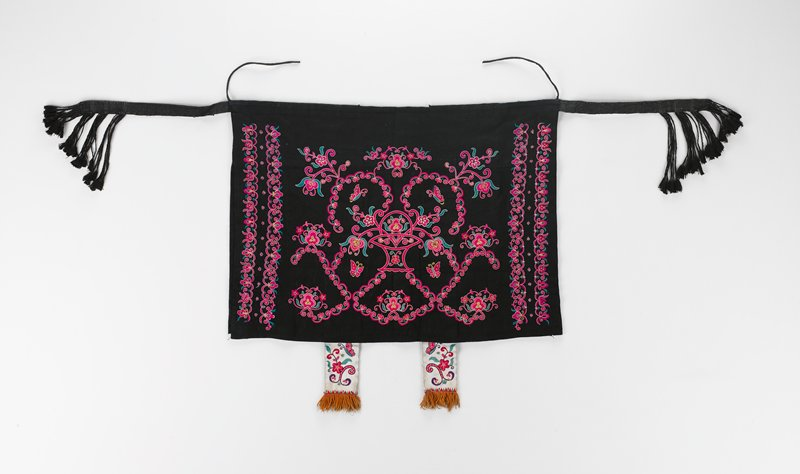 two black rectangular cloths sewn together at top with black tie straps on each side; top cloth has fuchsia embroidery work; two white embroidered bands hang down from the bottom