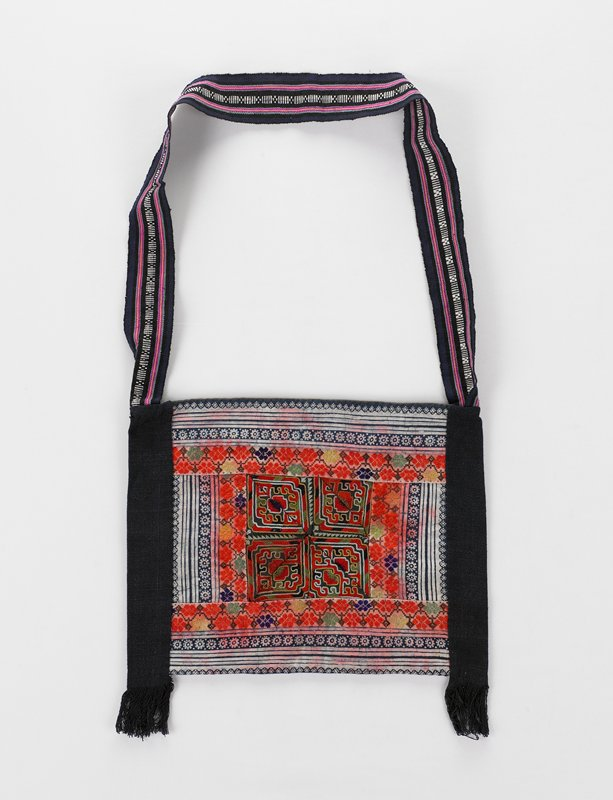 solid blue back; two bands on either side of front with a batik patterning around central embroidered design of rows of flowers and geometric designs; shoulder strap of blue, black, white and green bands attached to tops of side bands