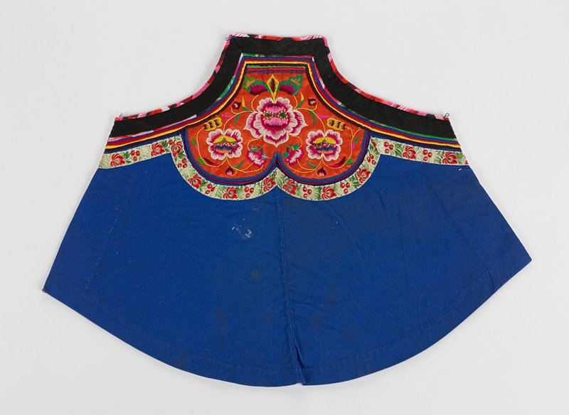 main part of apron is blue with banding and central panel at top and along top edge; three large pink and white flowers make up central design on orange field