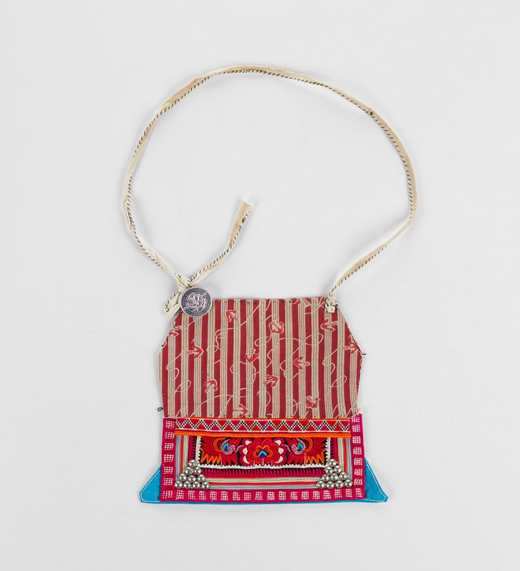 small apron made from red and tan fabric with small anchors; bottom of apron is decorated with fuchsia and orange embroidery and metal balls; turquoise corners on bottom; one coin fastened to tie loop in UL corner