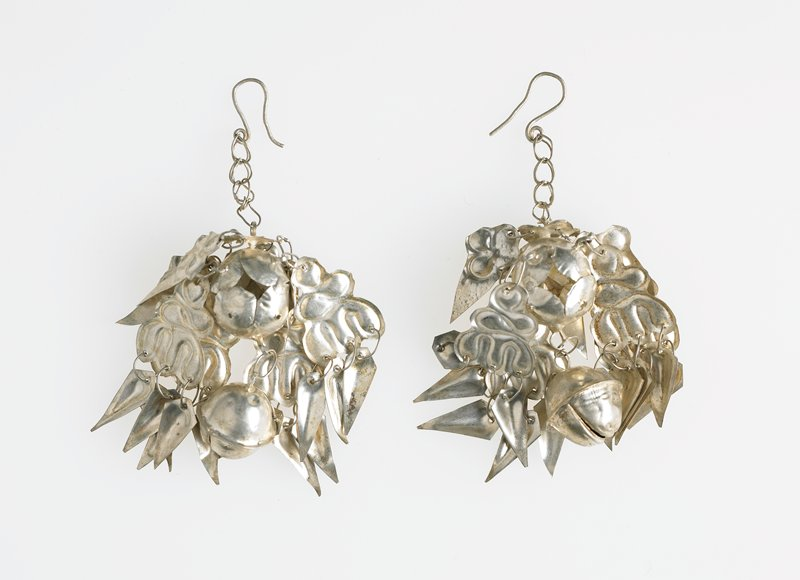central sphere with bell hanging from bottom and ear hook on top; eight pointed and curvilinear design pieces of thin silver hang from central sphere
