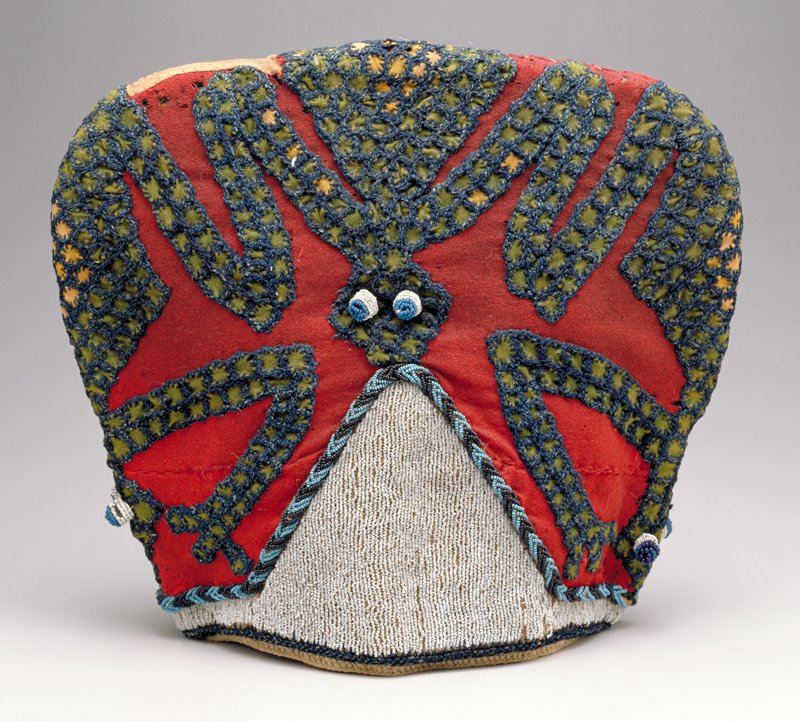 "woven raffia covered with red wool on which are three large frogs made of applique green and beige squares surrounded by blue wool blanket stitching; triangular area of white beads in front and back; each frog also has eyes of white beads with blue bead centers; raffia ties at center back Old accession tag inside cap : ""14030.0, NW Kamerun"" suggests that it may have come froma German collection. The shape of the cap is that of prestige caps worn in Bamoun, The iconography of frogs and perhaps snakes symbolized in the blue and green beadwork around each of the white areas is also typical for Bamoun. A hat with similar iconography, once worn by the Fon of Banso, is illustrated in Tamara Northern, THE SIGN OF THE LEOPARD. Storrs, CT: 1975., p. 74-cat. card"