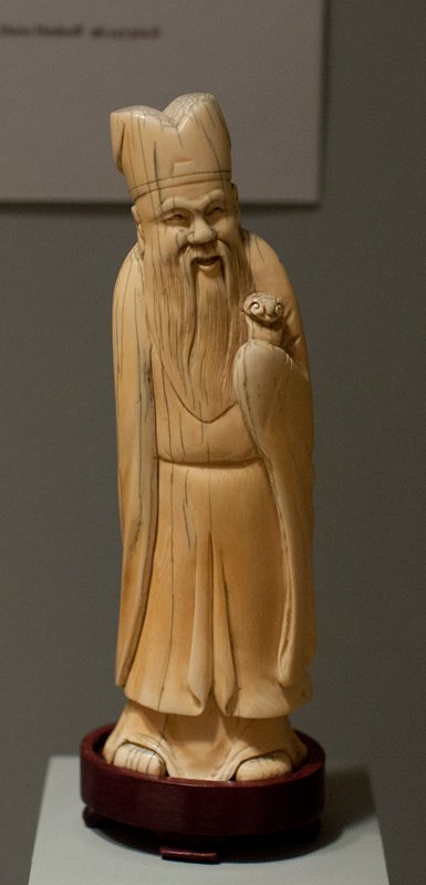 carved ivory figure of a bearded old man holding a scepter in proper left hand