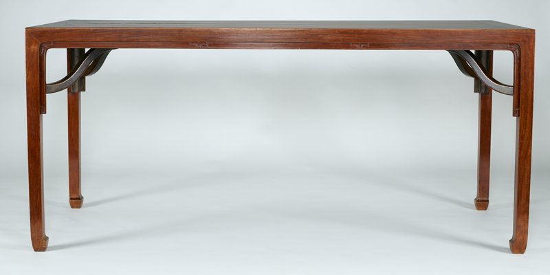 rectangular huang hua-li table; plain apron with abstract truncated cloud shaped spandrels and plain end apron; square legs with convex face moulded on either side to the front surface; double leg braces at short sides; framed single panel top