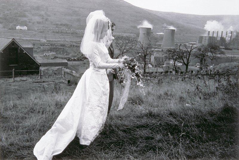 bride and groom walking on dirt lane; steaming smoke stacks in background.