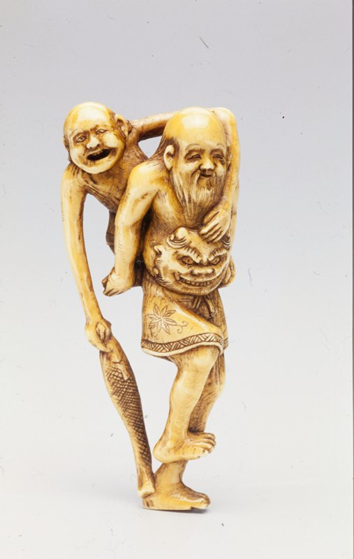 bearded man wearing short skirt with a demon mask at his waist carrying a short man with long arms on his back; short man carries a fish in his proper right hand