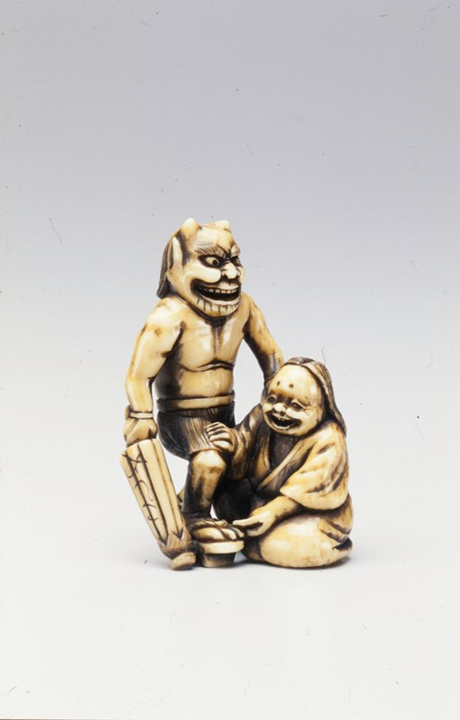 striding demon-man, with closed umbrella in proper right hand, rests proper left hand on shoulder of Okame, who adjusts the demon's sandal with his proper left hand and rests his proper right hand on the demon's knee