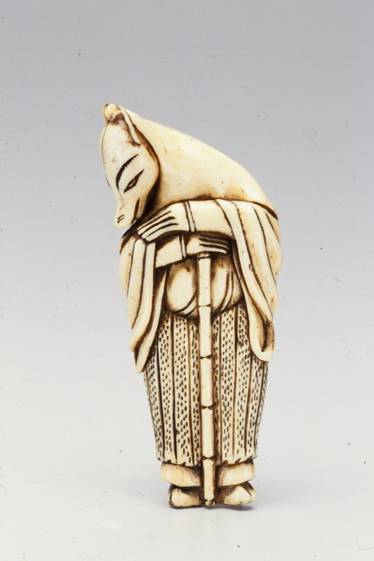 human figure with fox face wearing a hooded costume with long sleeve openings; head turned toward proper right shoulder; both hands resting on top of bamboo staff