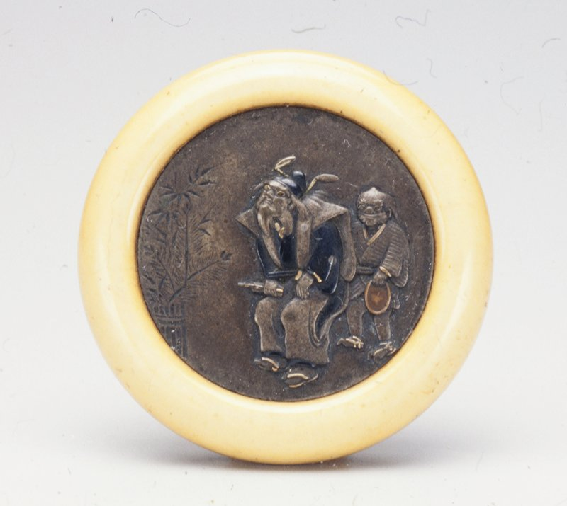 two figures depicted in low relief on metal disk; smaller figure at right holds a copper bowl in his proper left hand, bamboo fence with foliage behind it at left; ivory holder
