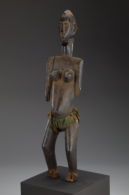 Standing female figure. Linear markings on body, scarification on face. Elongated neck. Cloth loin cloth.