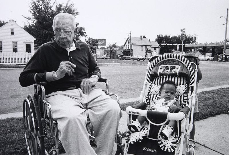 black and white photo of man in wheelchair and baby stroller outside