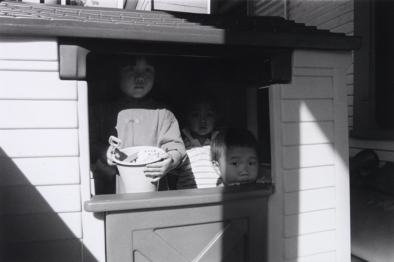black and white photo of three children standing inside playhouse