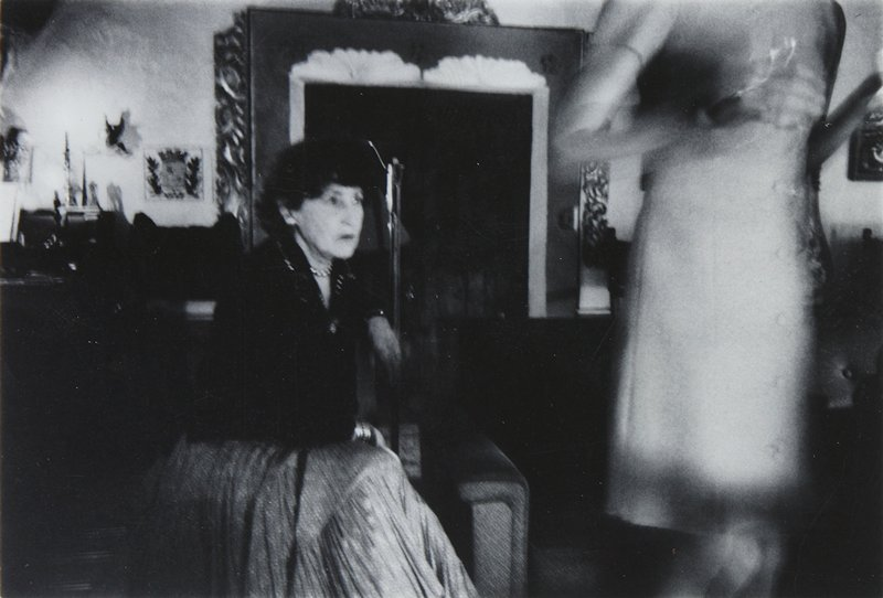 seated woman wearing dark blouse and printed skirt at left; another woman, torso, arms and thighs only visible, wearing a dress, at right; doorway visible behind women