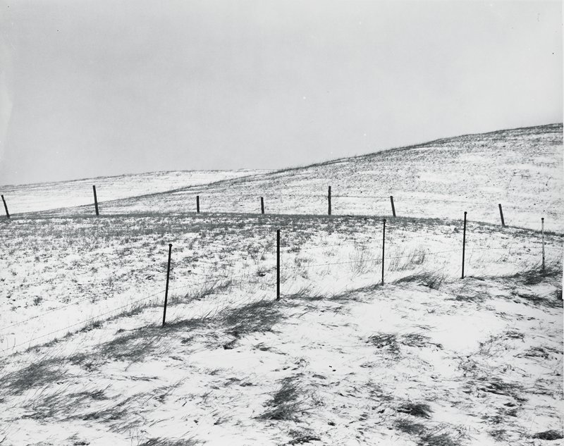 rolling field with two barbed wire fences and dusting of snow