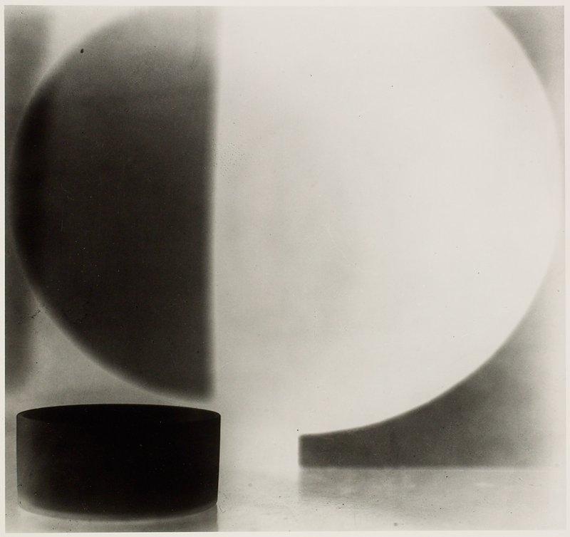 round black dish lower left corner; oval shape above sih 1/3 black, 2/3 white
