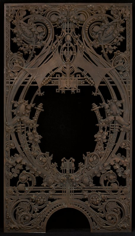 rectangular metal wicket; open center with elaborate scrolls, foliate motifs and floral motifs with a grid aroudn center opening; arched opening in base; five small holes on edge of each long side; some curved motifs resemble parts of gears