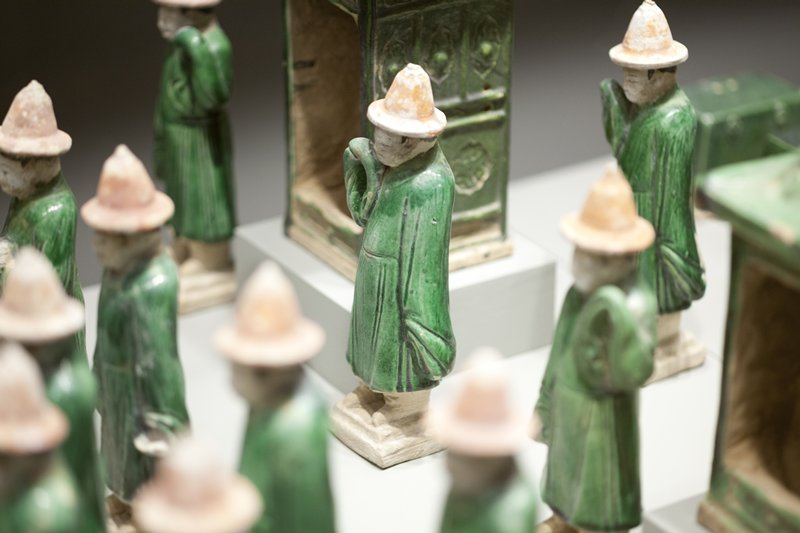 figure with green robe and red hat; very long sleeves; PR lower arm raised with end of sleeve handing down