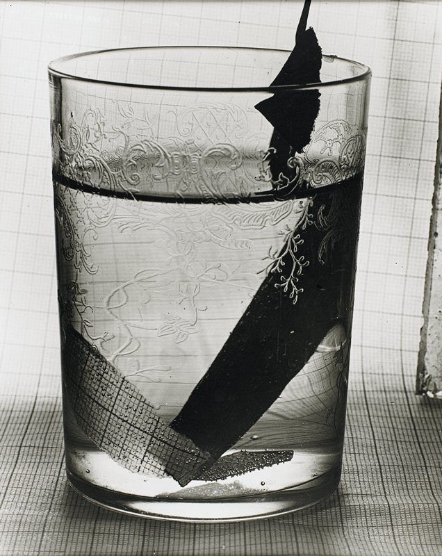 etched glass water tumbler sitting on graph paper