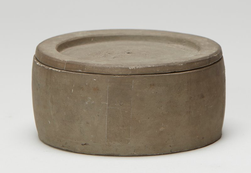 Yixing ware; grey container and lid; lid has small hole in center; stamped design in center of lid with geometric and floral motifs