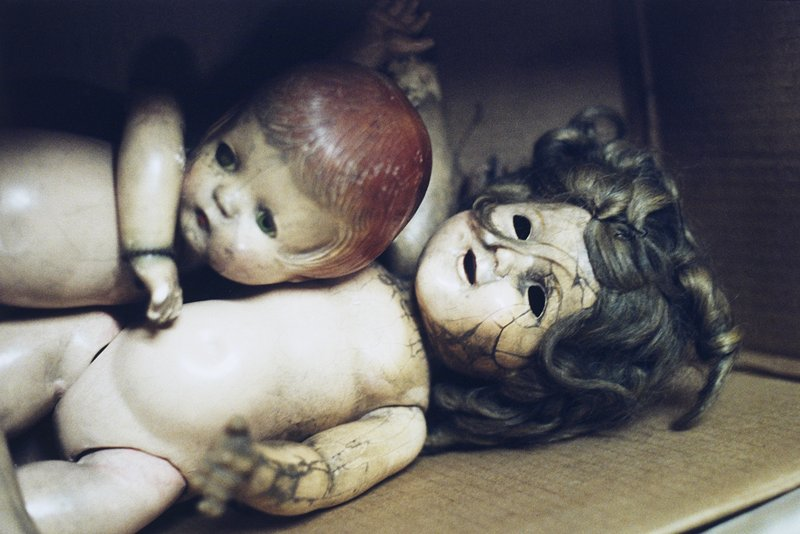 Two damaged dolls in a cardboard box; doll at R has matted hair, missing eyes and cracked face; doll at L has molded red hair and arm across chest