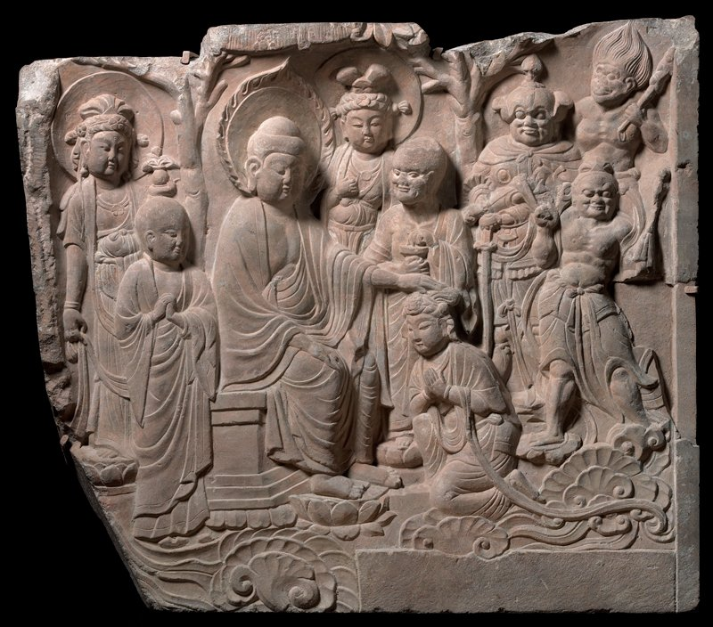 deep relief carving; Buddha at L seated on a throne with PL hand on head of kneeling Bodhisattva with clasped hands; 7 other figures stand behind and to R and L