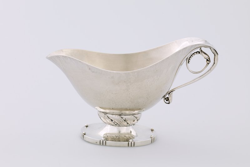 silver sauce boat unadorned body seated on a wreath and tapered oval base with eight studs at edge; handle formed by an opening seedling curled under back rim of boat; forms a set with .29.2 ladle