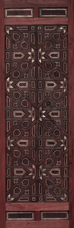 Door Panel, Mamluk dynasty, wood carved with geometric and arabesque patterns, inlaid with ivory. Panel has modern mount and is set in seperate base which has four small decorative wood panels inset. Remounted 1984.