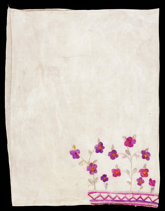 White cotton ground with silk embroidery at head opening; floral design in pink and purple with pale green stems and leaves; zig zag pattern around opening.