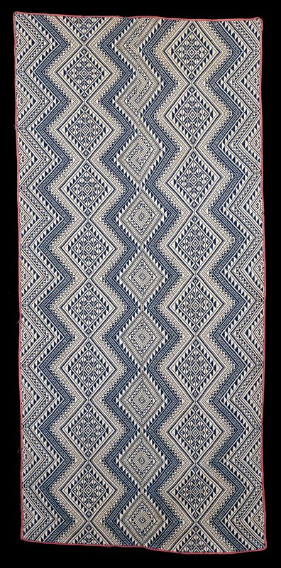 woven fabric; navy blue on white ground; geometric design; 2 panels; seamed center; edges bound with light red