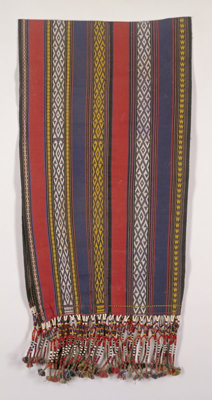 long panel; folded in half, joined along on edge; stripes blue, red, yellow, white alternating with patterned stripes; white and yellow on green-blue ground; elaborate wrapped fringe