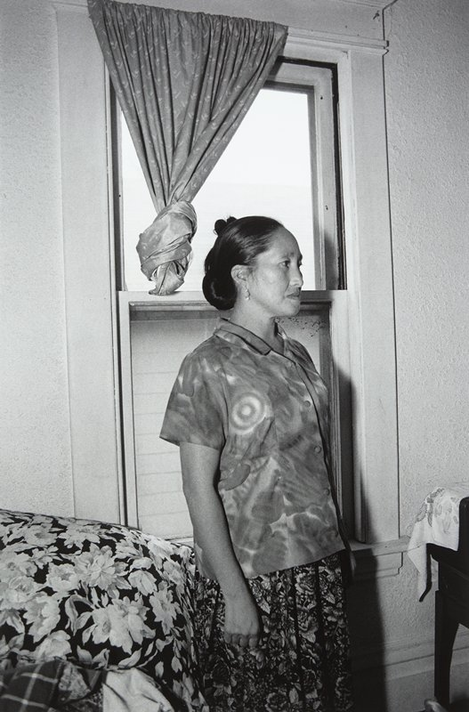 black and white photo of woman in print blouse and skirt standing in front of window with knotted curtain