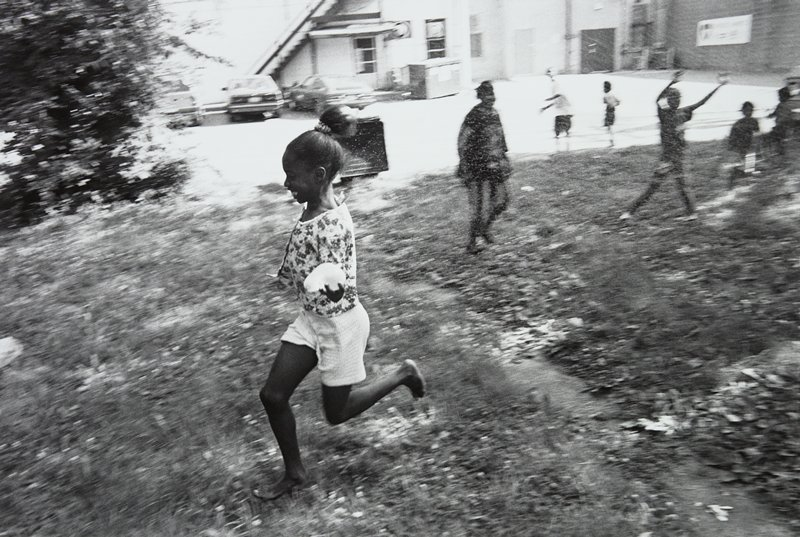 black and white photo of young girl in shorts running while holding water balloon
