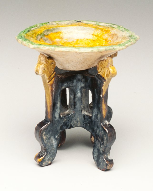 Tomb furniture; small saucerlike basin with decorative scalloped edge; edge glazed green, center tan; stand with 4 legs radiating from central support; basin supports glazed yellow with legs glazed brown
