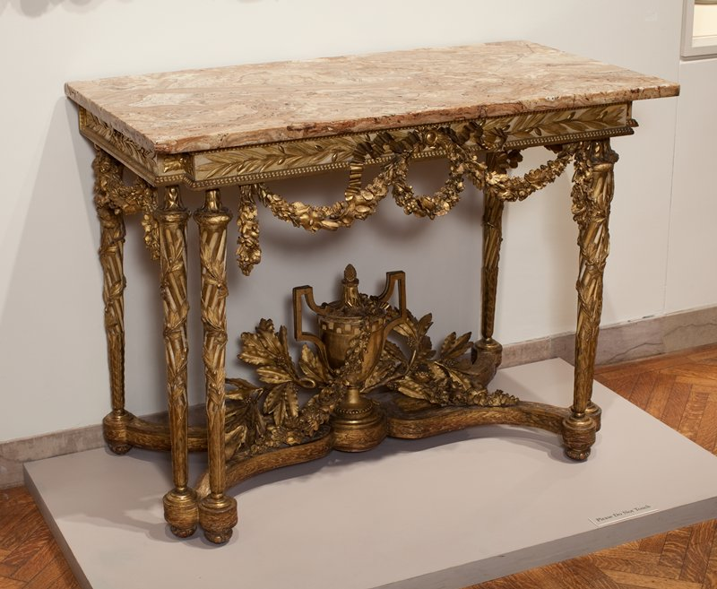 Carved wood and gilded console top is of breche d'Aleppe marble; frame and stretchers covered with a profusion of ornament; legs in front are double - all entwined with laurel. The stretcher supports a large classical vase with a Greek border surmounted with an acorn finial and draped with floral garlands and laurel sprays. On every part of the table are eloborate floral swags. Louix XVI period.