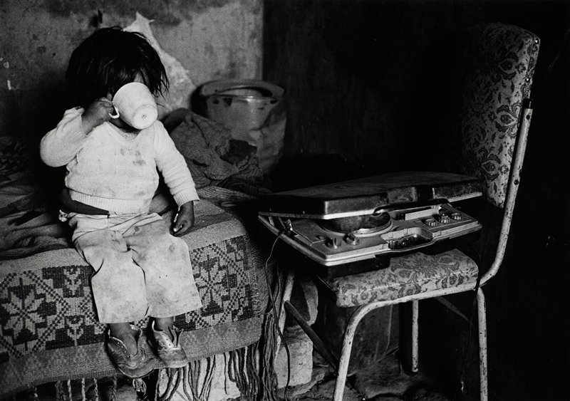 young child sitting on a bed and drinking from a cup