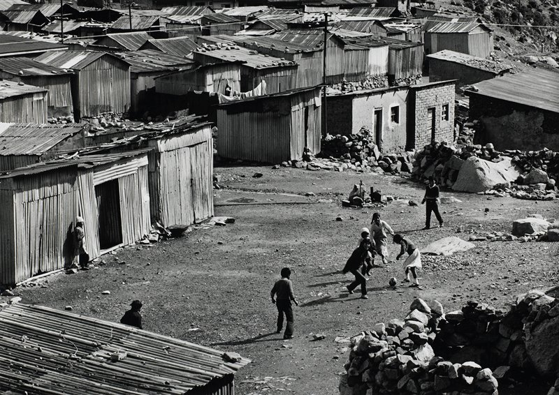 children playing soccer, LRC; shacks in the background