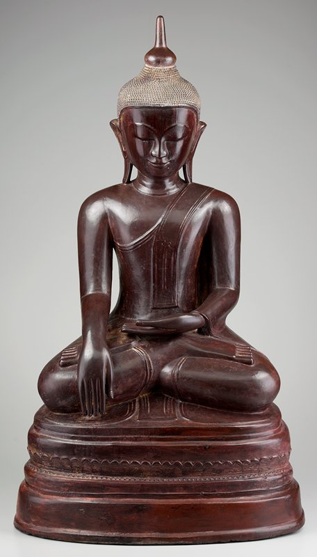 seated cross-legged Buddha with PR hand pointing downward and PL hand palm up on lap; head bent slightly downward, eyes closed; brownish-red color