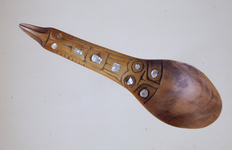 Spoon or ladle of yellowish horn probably 'bighorn sheep'. The handle is flat and roughly ornamented with eye and feather-like ? designs with mother-of-pearl inlays.
