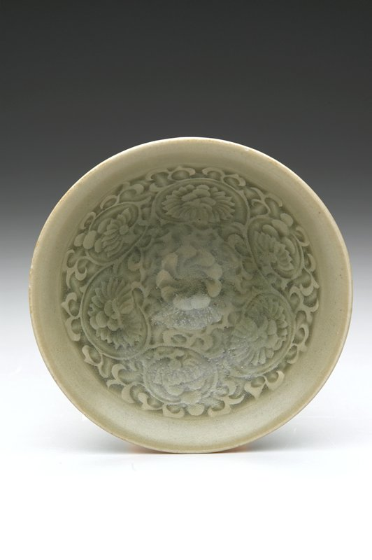 bowl, porcelain, grey green celadon; impressed underglaze design of scrolling flowers.