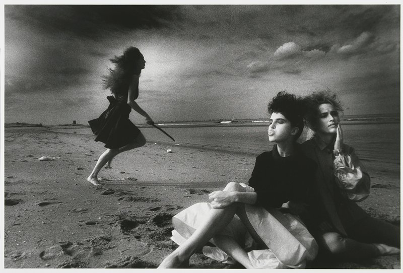 woman with long bushy hair, wearing a knee-length dress and holding a stick in her PR hand, running at L; 2 women at R, seated, leaning against each other woman at L wears black top and light skirt, blowing a bubble with gum; woman at R holds her PL hand on her chin; on a beach