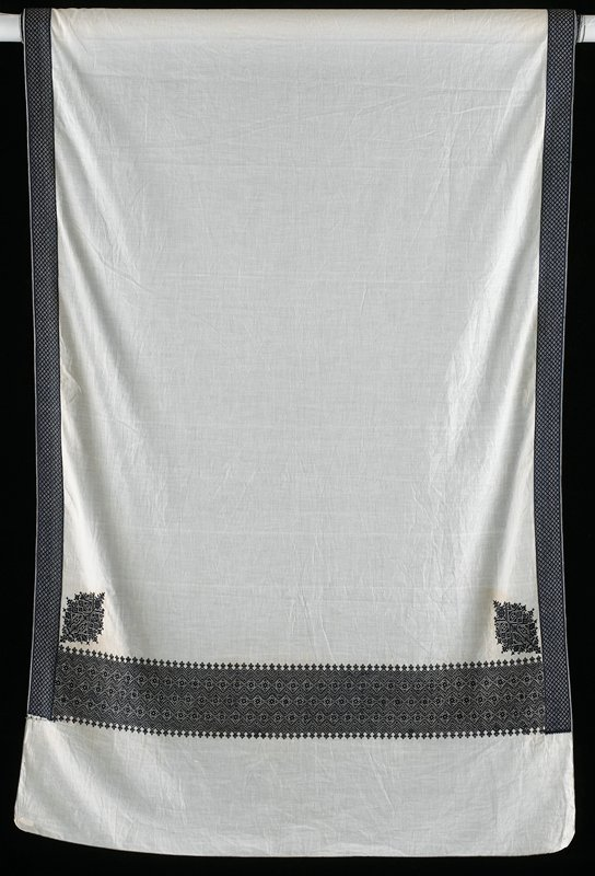 thin white cotton with dark blue embroidery; border on long sides; geometric pattern with flowers at short sides with medallions at corners