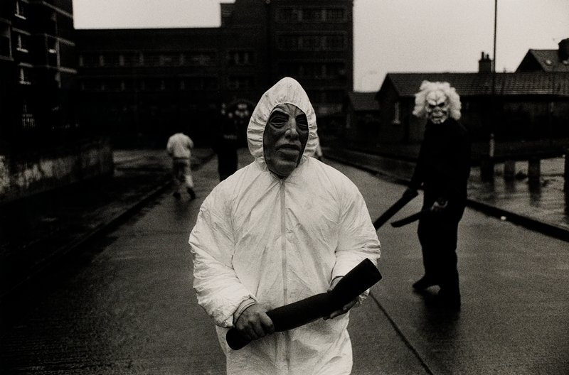 figure wearing a mask and a hooded white jacket at center; another masked figure at right