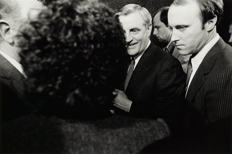 Walter Mondale, right, with face partially hidden by head of curly haired woman in foreground
