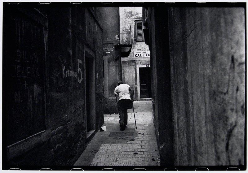 one leg man with cane walking away through alley