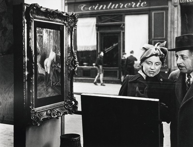 man and woman looking at art in a shop window; woman looks at object in foreground, man looks at Impressionist-style painting of a nude wearing stockings at L