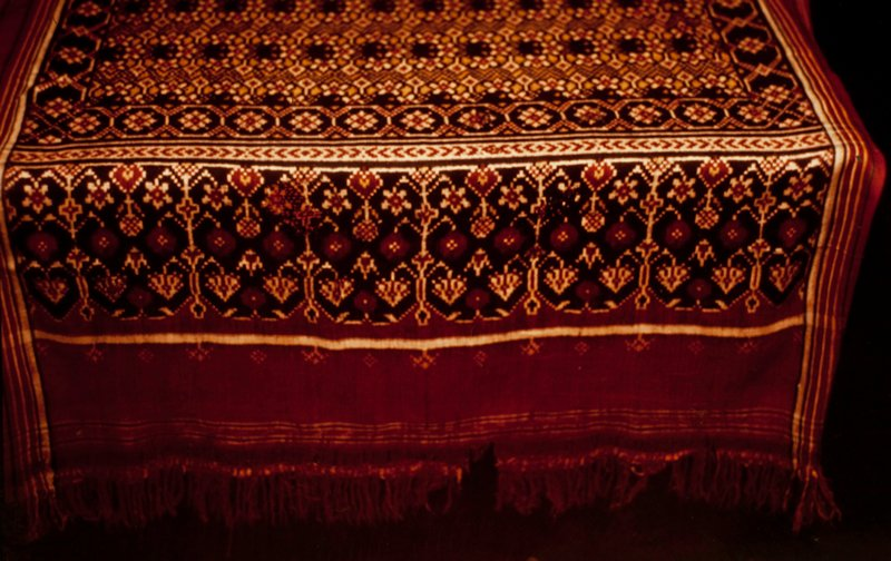 Potala (double ikat) silk panel with all-over geometric pattern in yellow, red, green, and brown. Finished at each end with wide borders and fringe; possibly a sari.