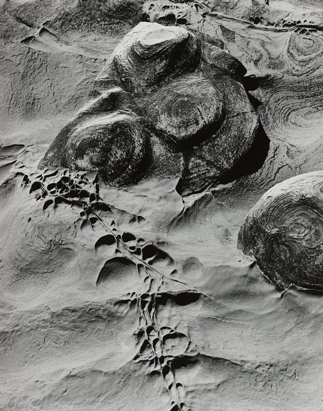 abstracted image; sand with two large rocks with circular patterns; round tracks in sand, LLC