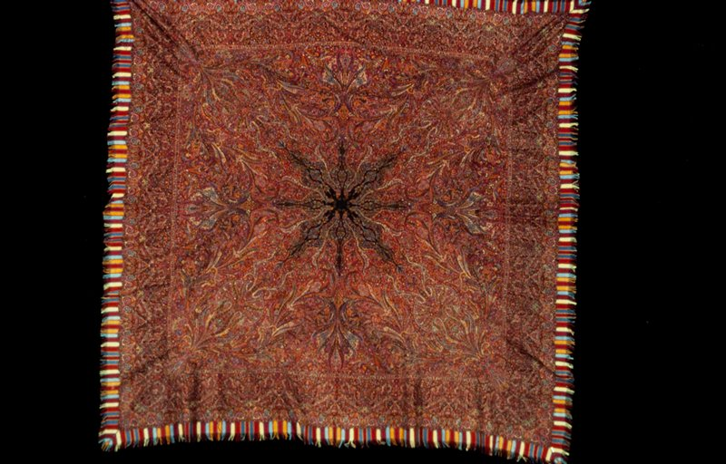 kussaba or square shawl; the ground is of black wool, parts of which have been woven separately and fastened together; shawl is completely covered with floral and arabesque designs; border woven separately and added; supplementary border of fringed strips of colored woolen; the design has been outlined in embroidered stitch; alike on both sides