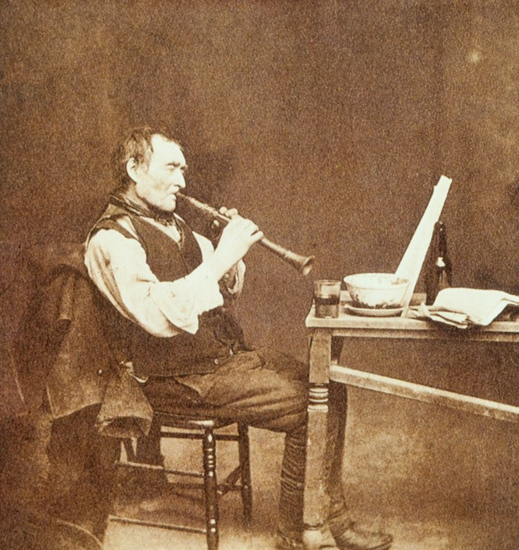 man seated at a table plays a horn (oboe or clarinet?), his music perched between a bowl and bottle