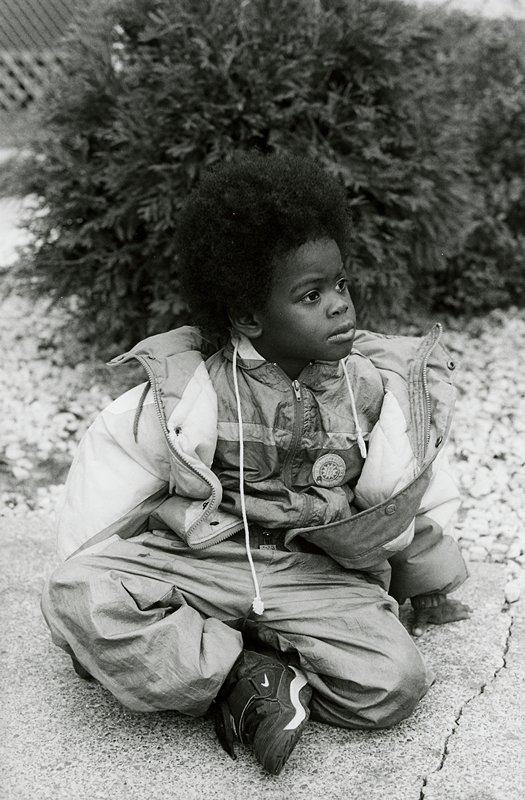 black and white photo of seated child with afro, wearing jogging suit and coat